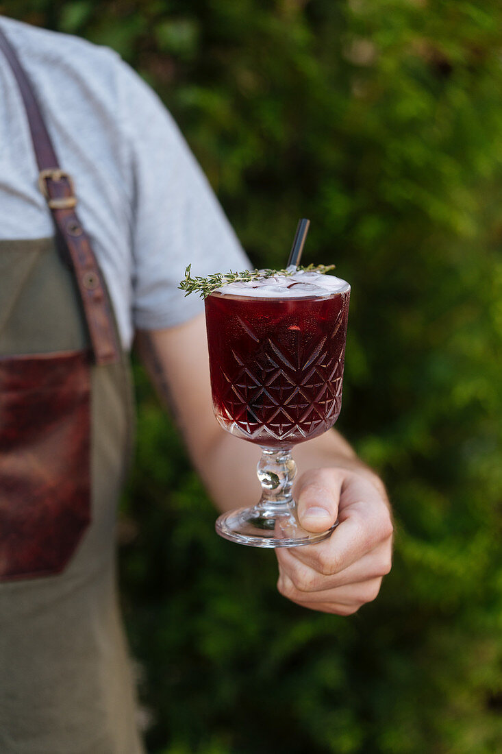 Person holding fresh tasty red cocktail with straw in glass in green garden