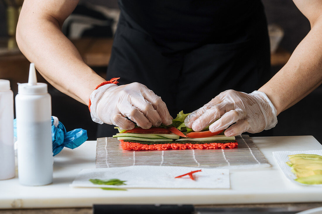 Cook in gloves kneading red spicy stuffing on table with greens fish and sauces