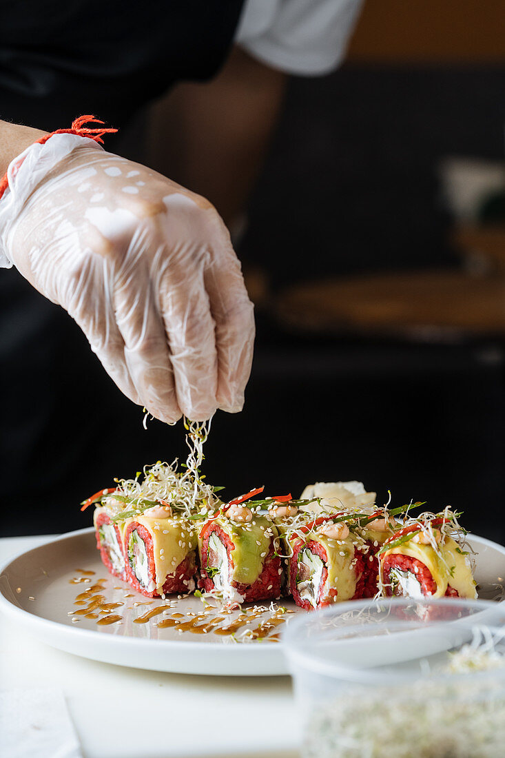 Cook in gloves decorating fresh tasty sushi with greens