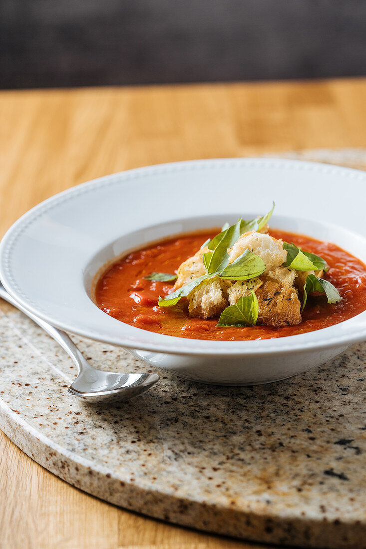 Appetizing fresh tomato soup with greens on white plate on marble stand