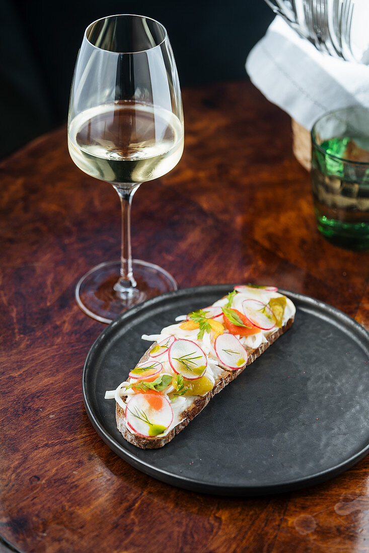 Colorful sandwiches with red radish sliced and herbs in white sauce with wine