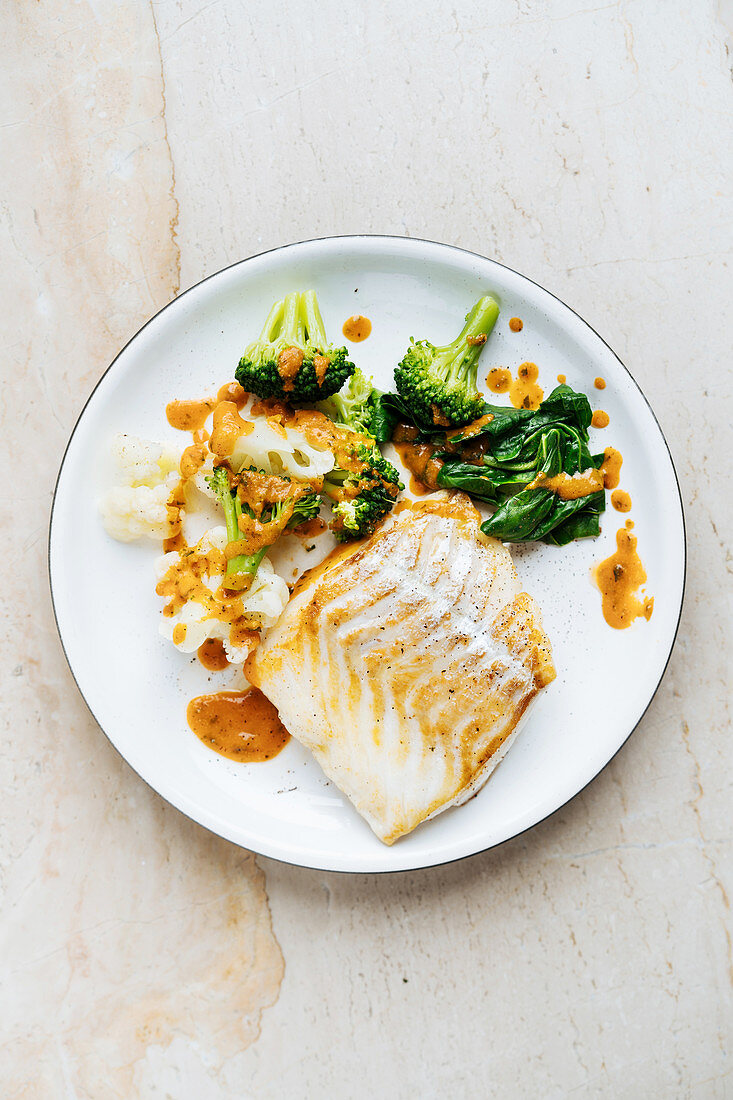 Fish with green and broccoli sprinkled with red sauce on white plate