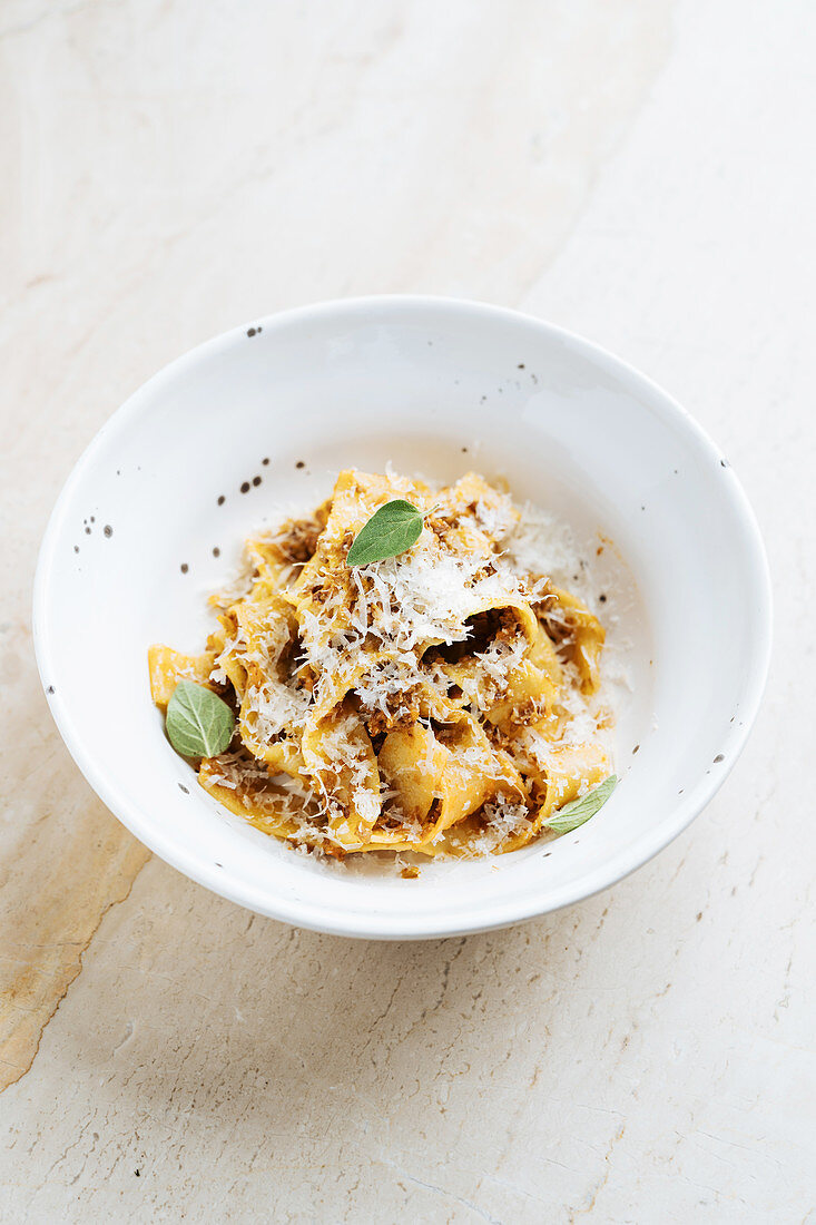 Dish with wide pasta sprinkled with cheese and decorated with fresh mint