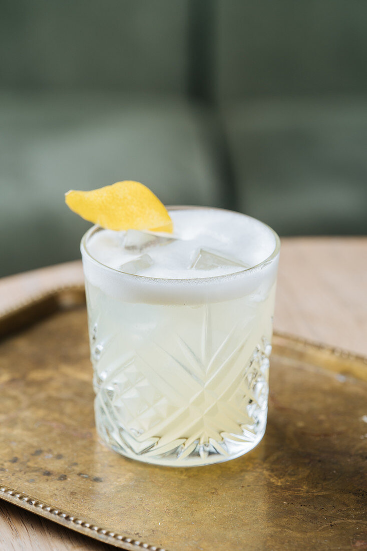 Alcohol cocktail with foam in stylish glass decorated with lemon zest