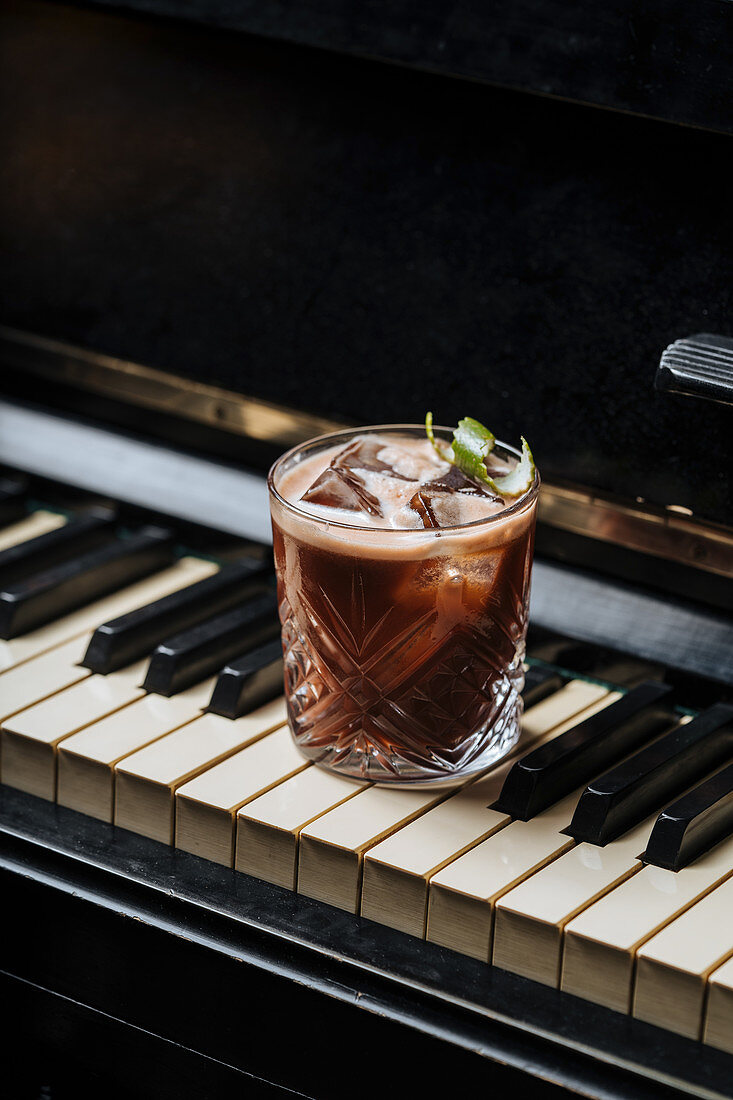 Glass of cocktail with ice resting on a piano keys
