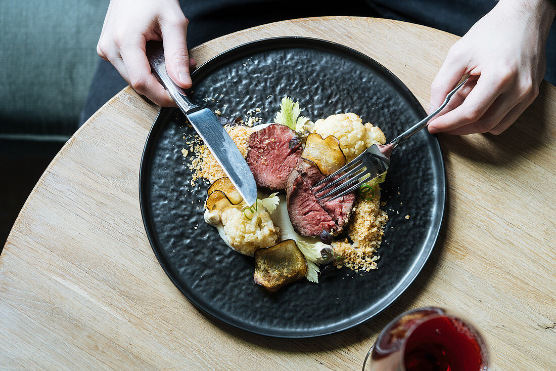 Person with plate with roast beef slices on creamy sauce with cauliflower and fried chips