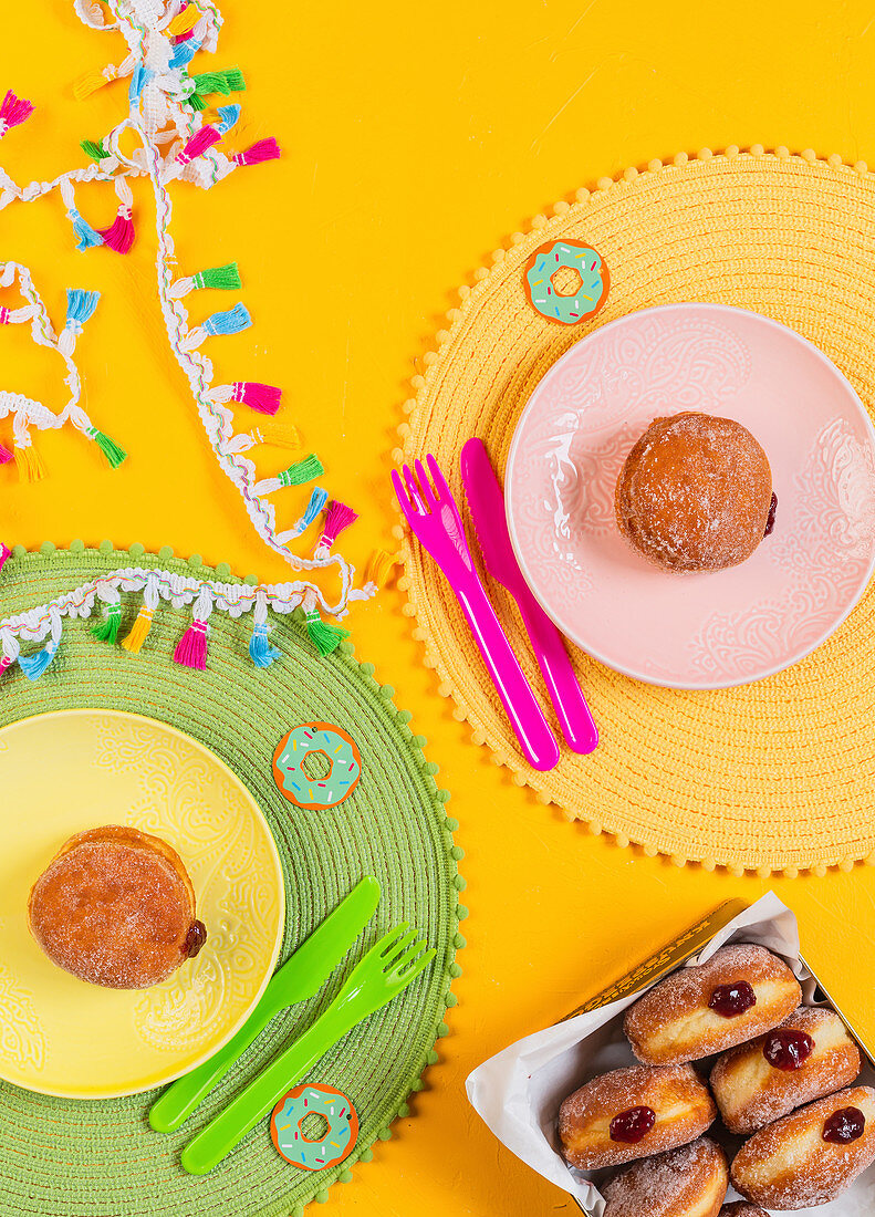 Donuts with jam, served on colorful plates, during kids party