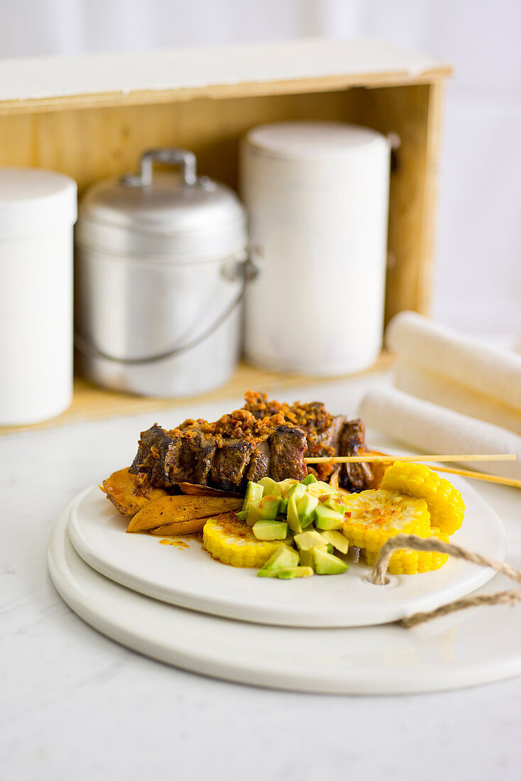 Spicy veal heart kebabs on sweet potatoes, sweetcorn and avocado