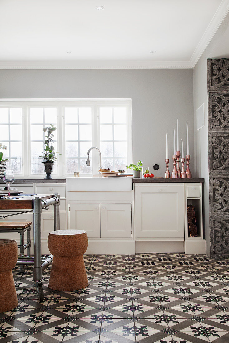 A vintage dining table and cork-shaped stools in a country house kitchen with decorative floor tiles