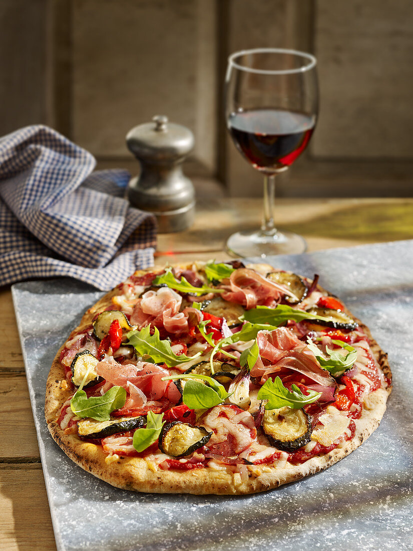 Pizza with rocket, courgette, chorzo, parma ham, mozzarella red peppers