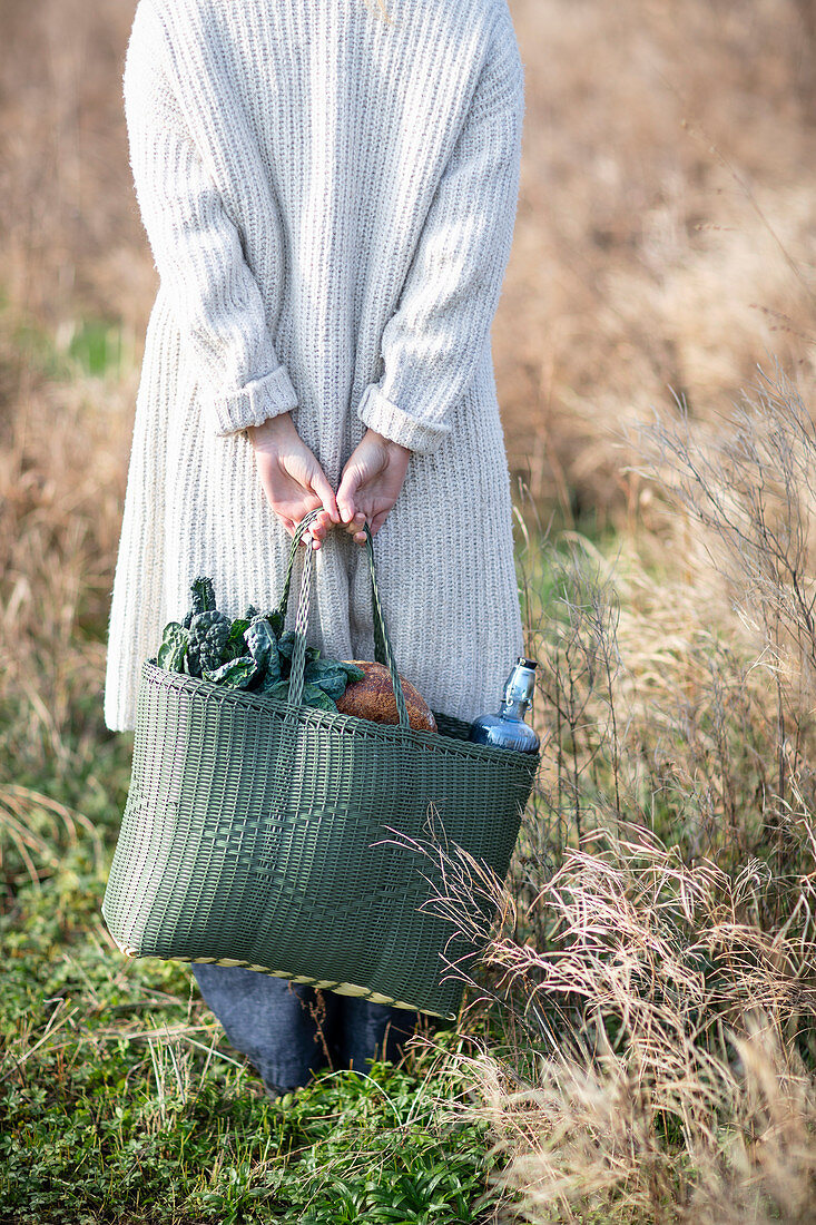 A woman in a field with a shopping bag