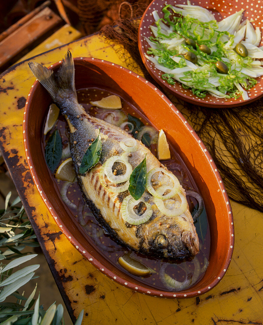 Fried gilt-head bream with onions and bay leaves