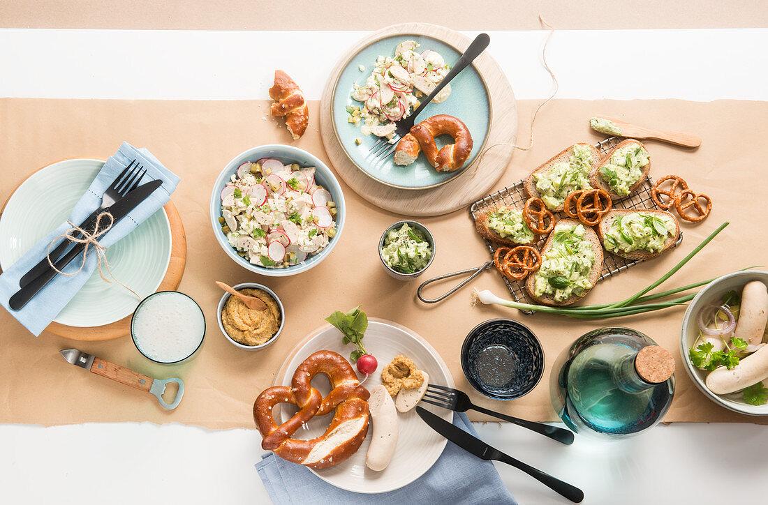 Bavarian supper with white sausage, radish salad, obazda cheese and pretzels