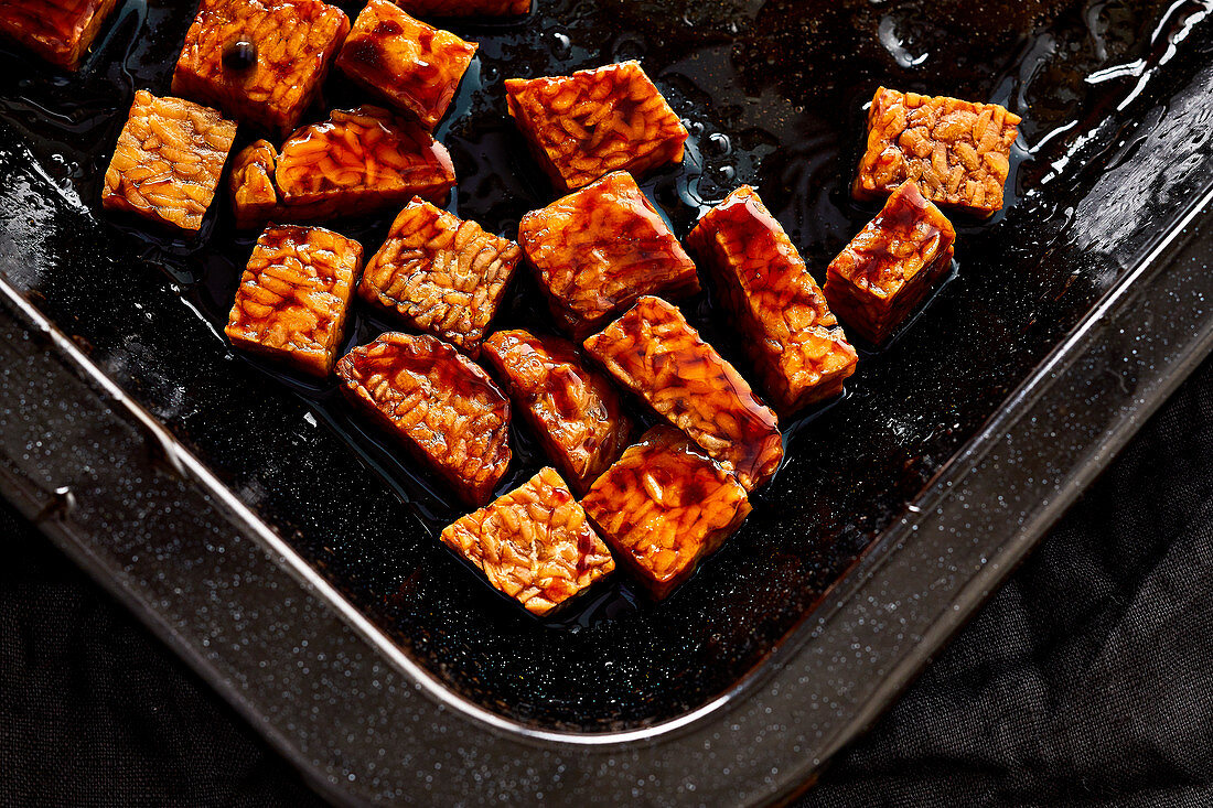 Oven-baked tempeh pieces drizzled with soy sauce