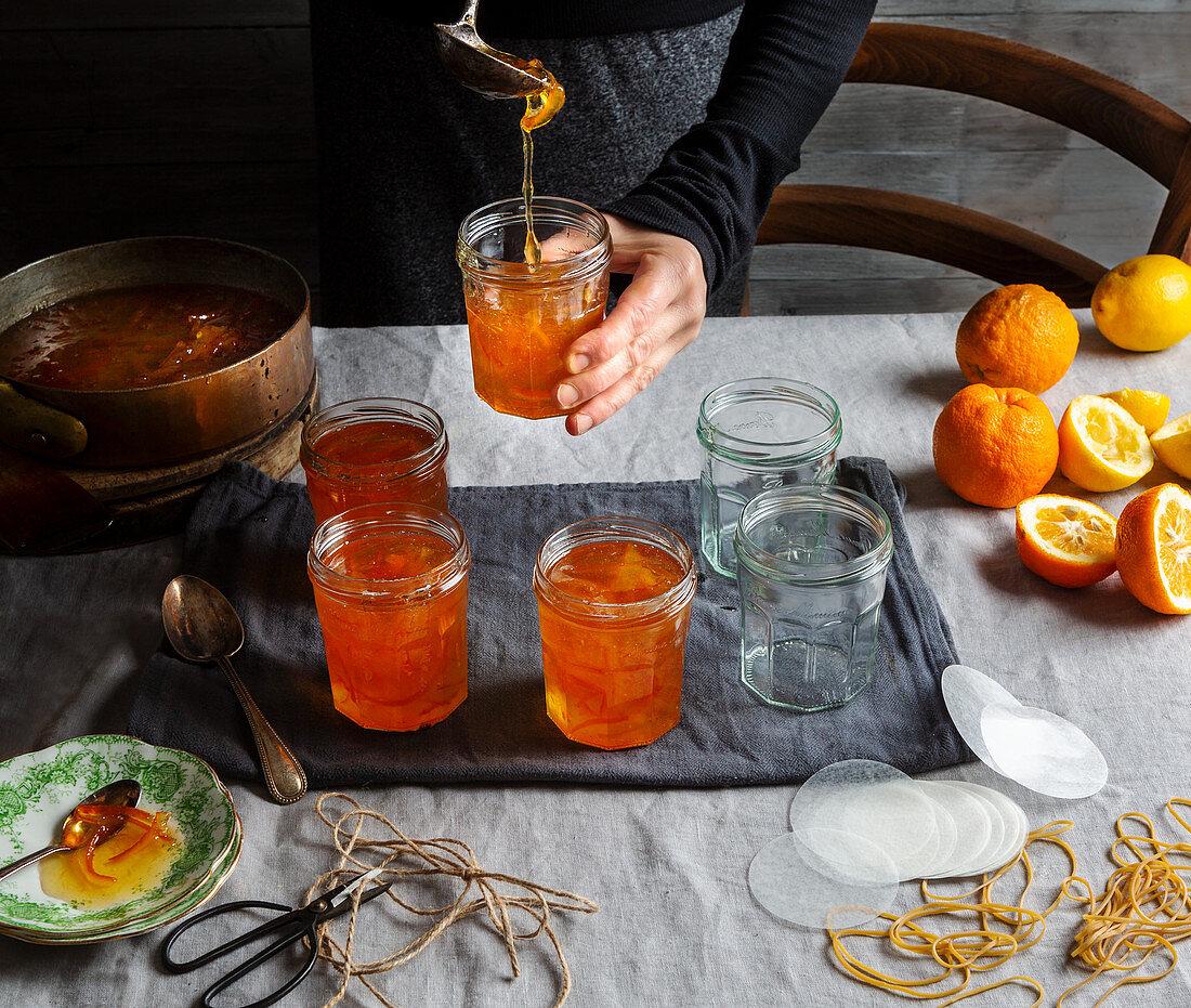 Preparing orange jam from Seville oranges: pouring jam into glasses