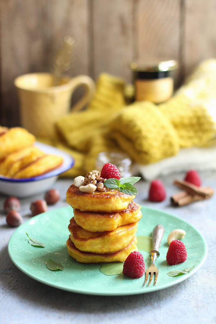 Pancakes with syrup, raspberries and nuts