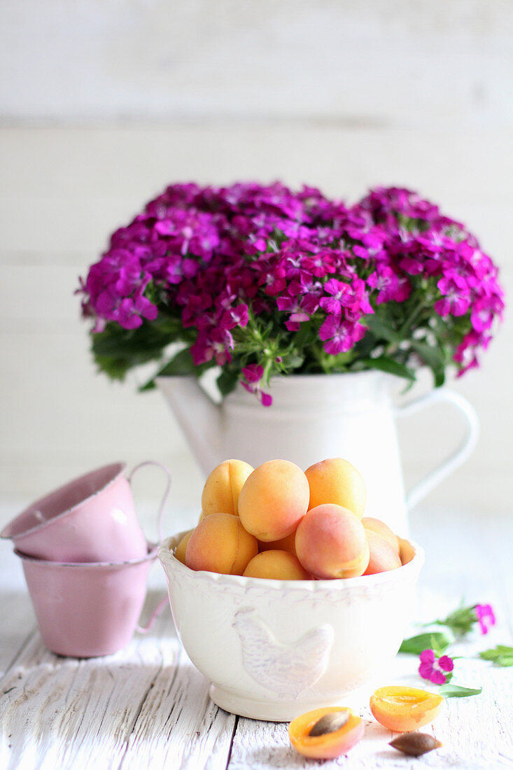 An arrangement of apricots in a porcelain bowl with a bouquet of carnations