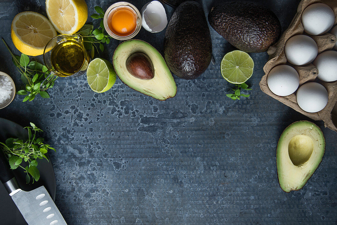 Ingredients for a low-carb breakfast: eggs, avocado and herbs