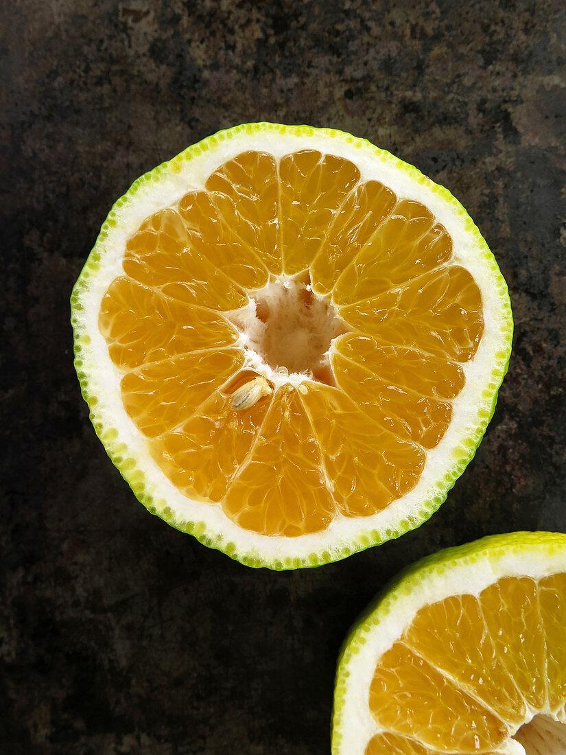 A halved ugli fruit on a dark surface