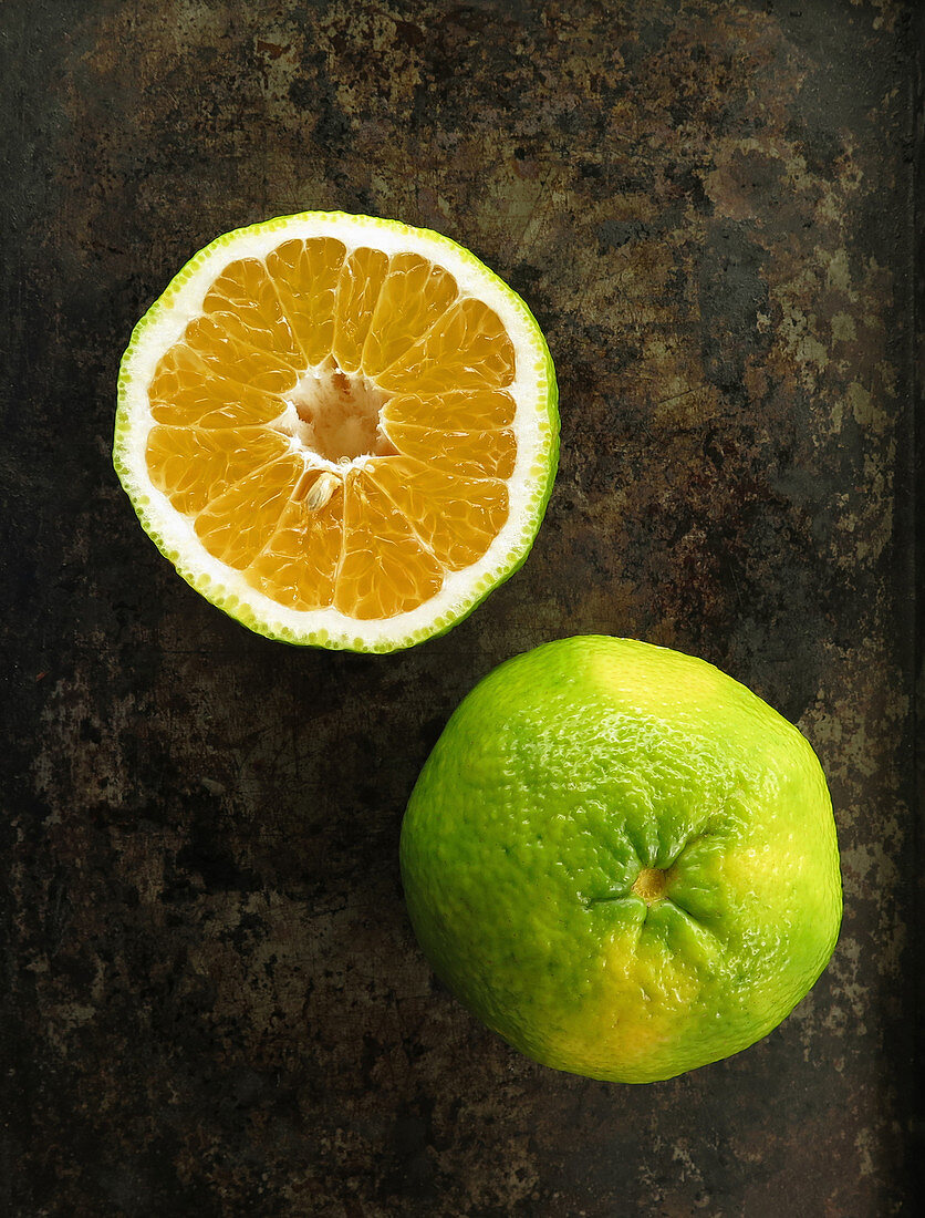 A halved and whole ugli fruit on a dark surface