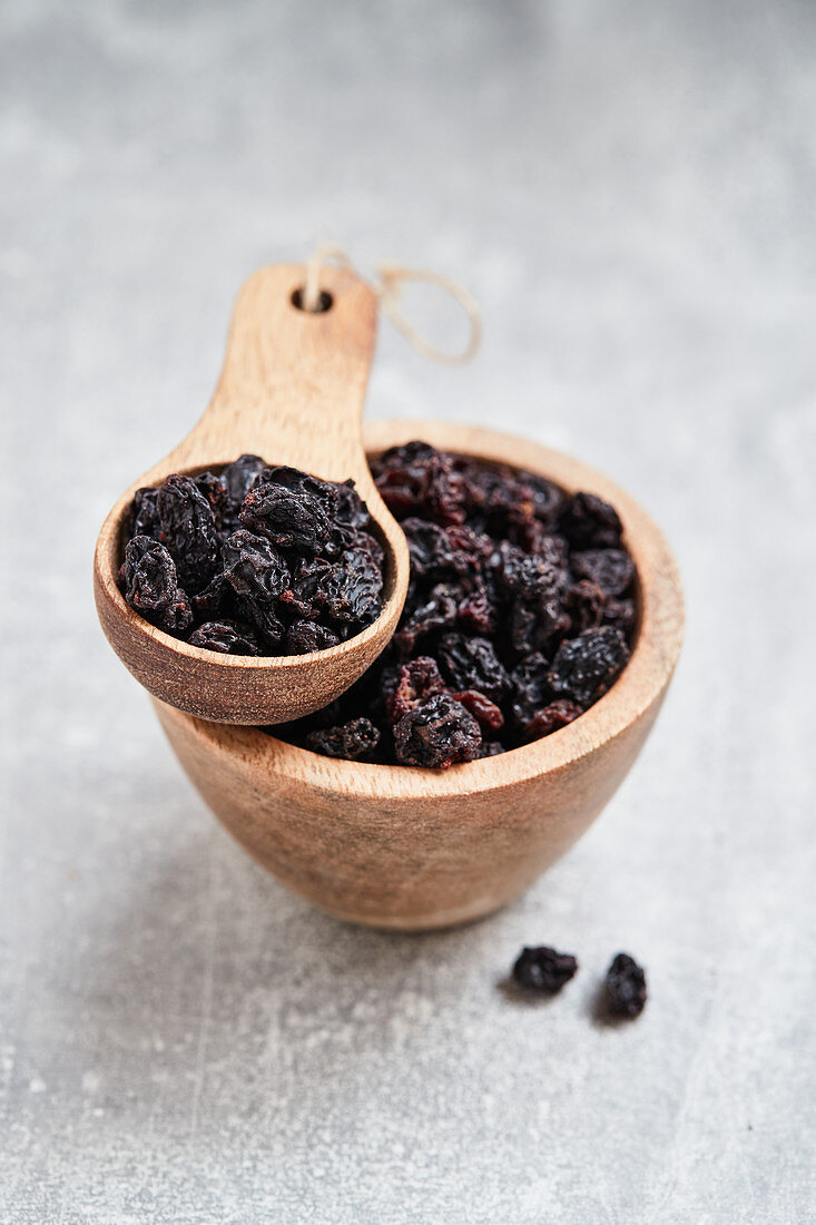 Currants in a wooden bowl and a wooden scoop