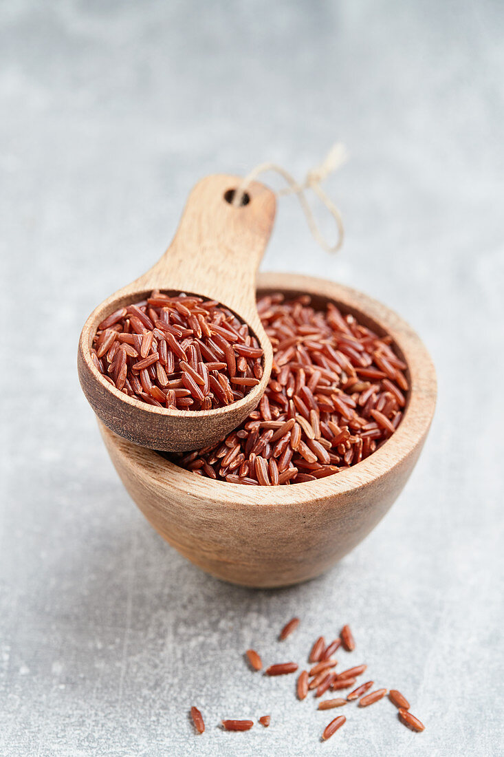 Red rice in a wooden bowl and a wooden scoop
