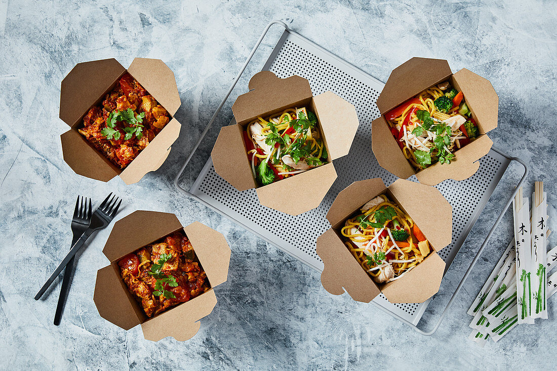 Chilli chicken and oriental noodles with vegetables in take away boxes