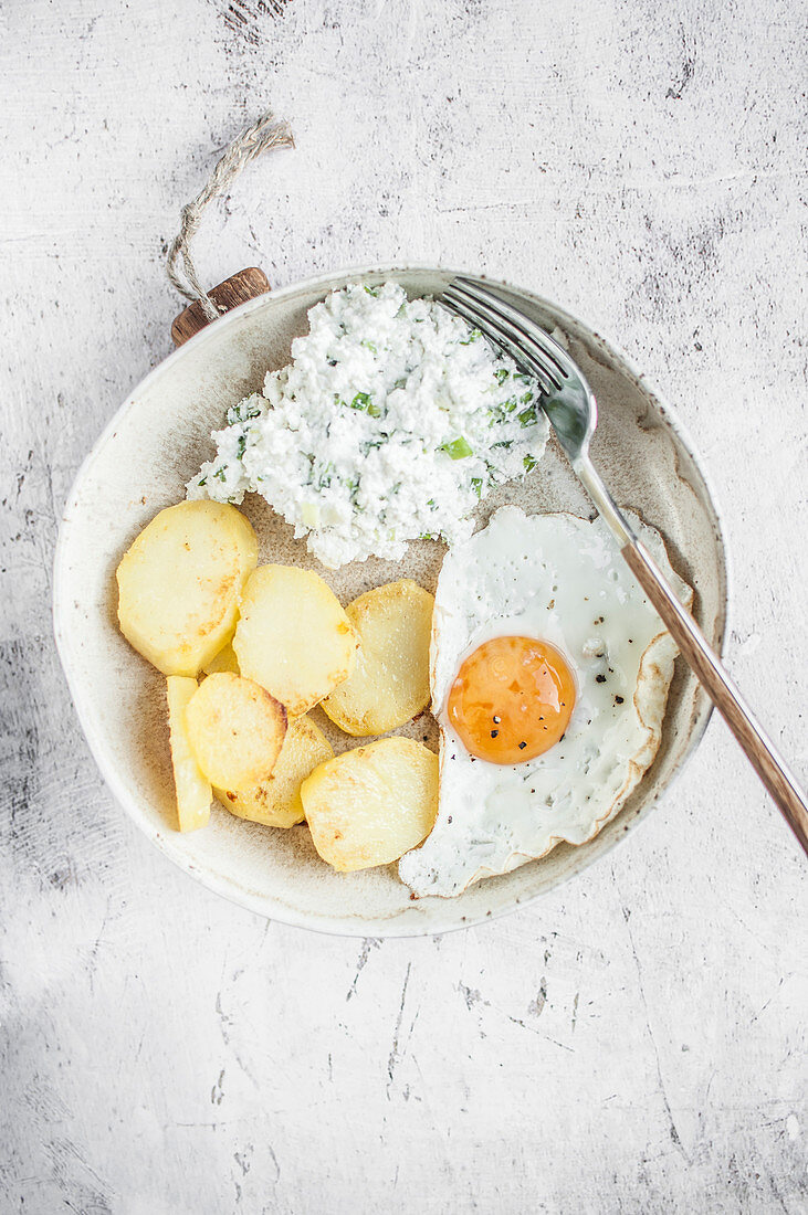 Simple vegetarian lunch. Fried egg, fried potatoes and cottage cheese with green onion.