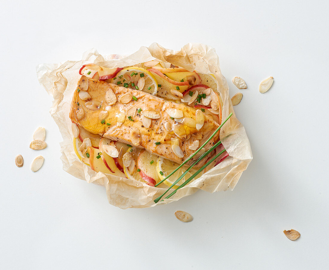 Salmon steak with honey, apple and lemon in parchment paper