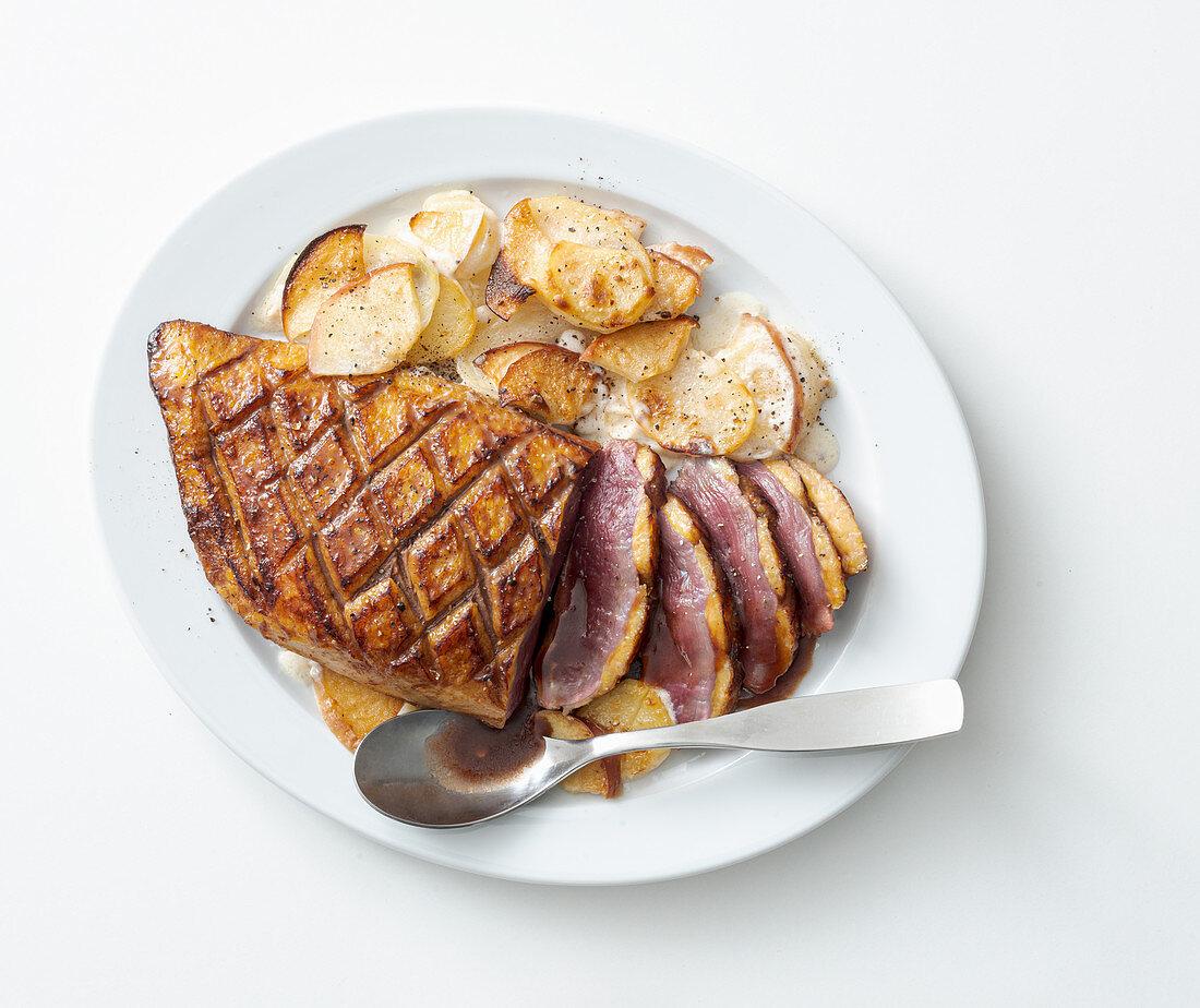 Duck breast a honey glaze on a potato and apple gratin