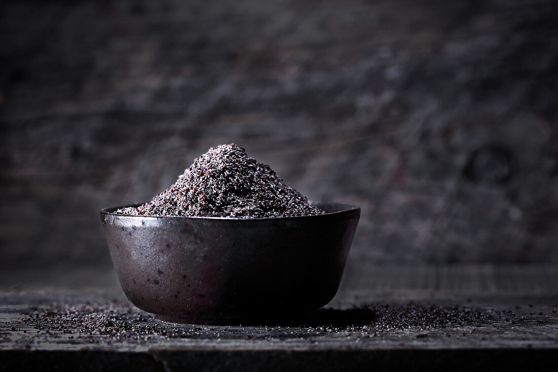 Poppyseeds in a black bowl against a black background