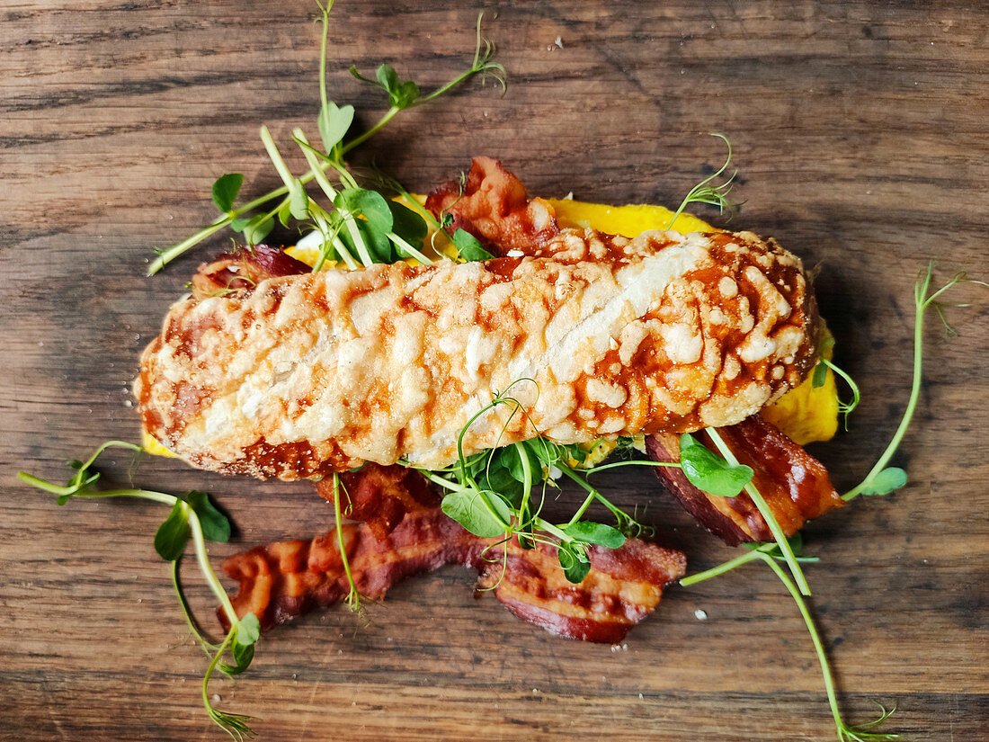 A cheese roll filled with bacon, egg and pea sprouts