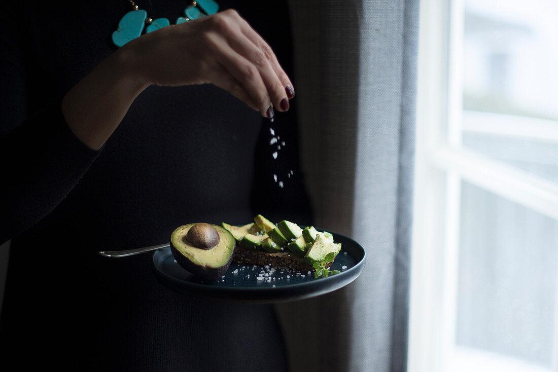 A woman standing at a window sprinkling fleur de sel onto avocado bread