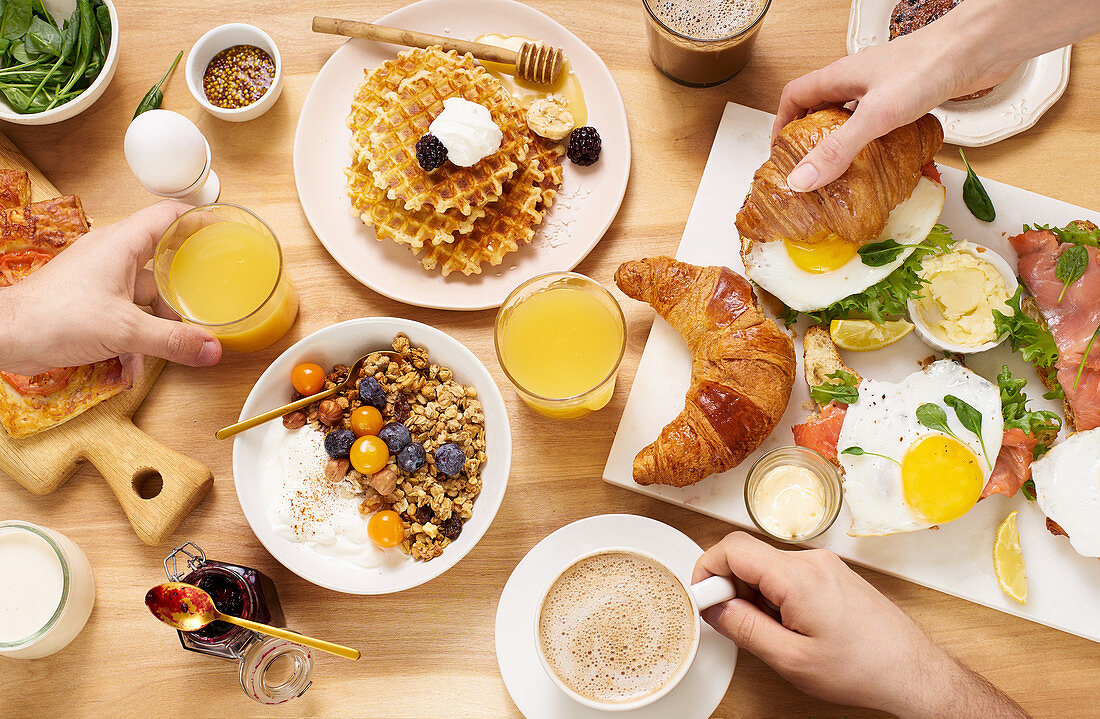 Healthy sunday breakfast with croissants, waffles, granola and sandwiches