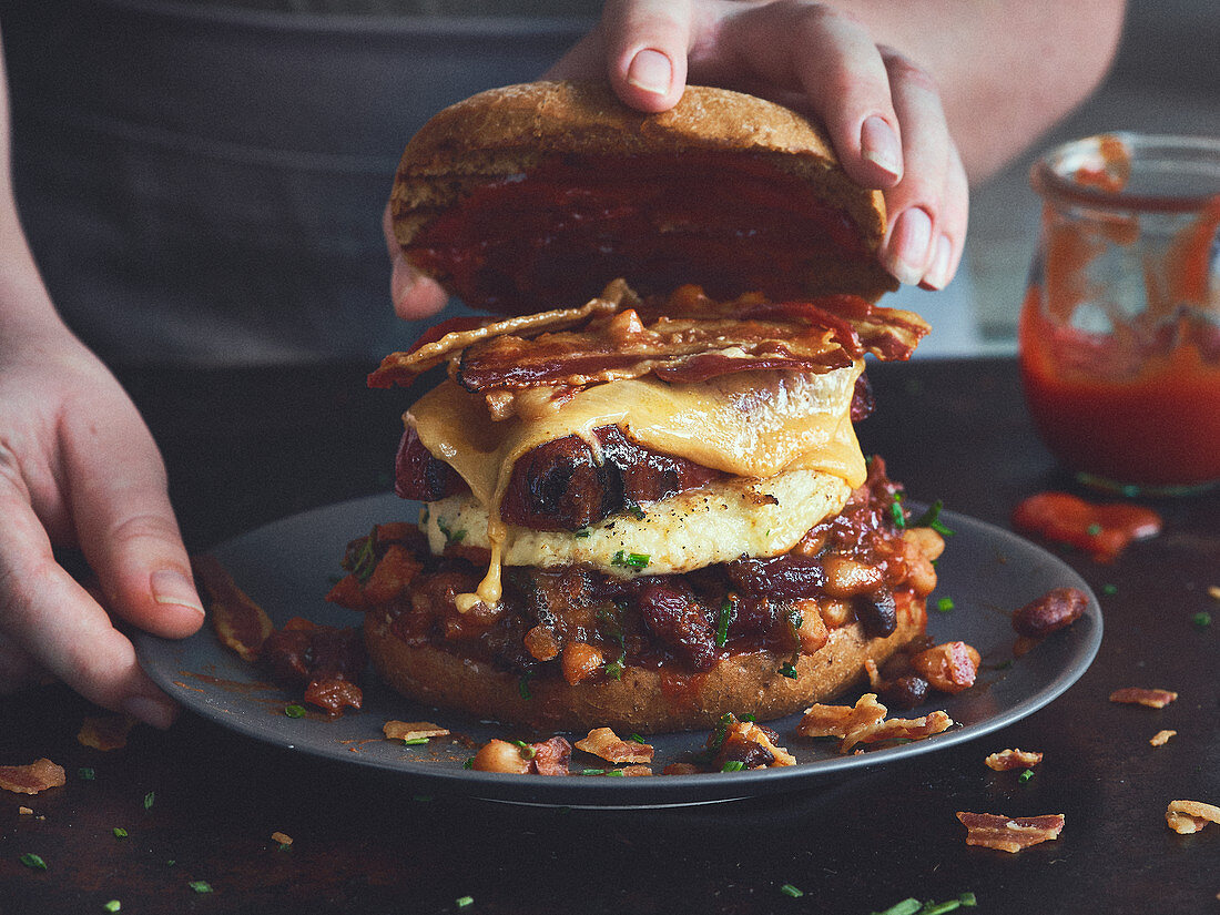 An English breakfast burger with sausages, bacon and baked beans