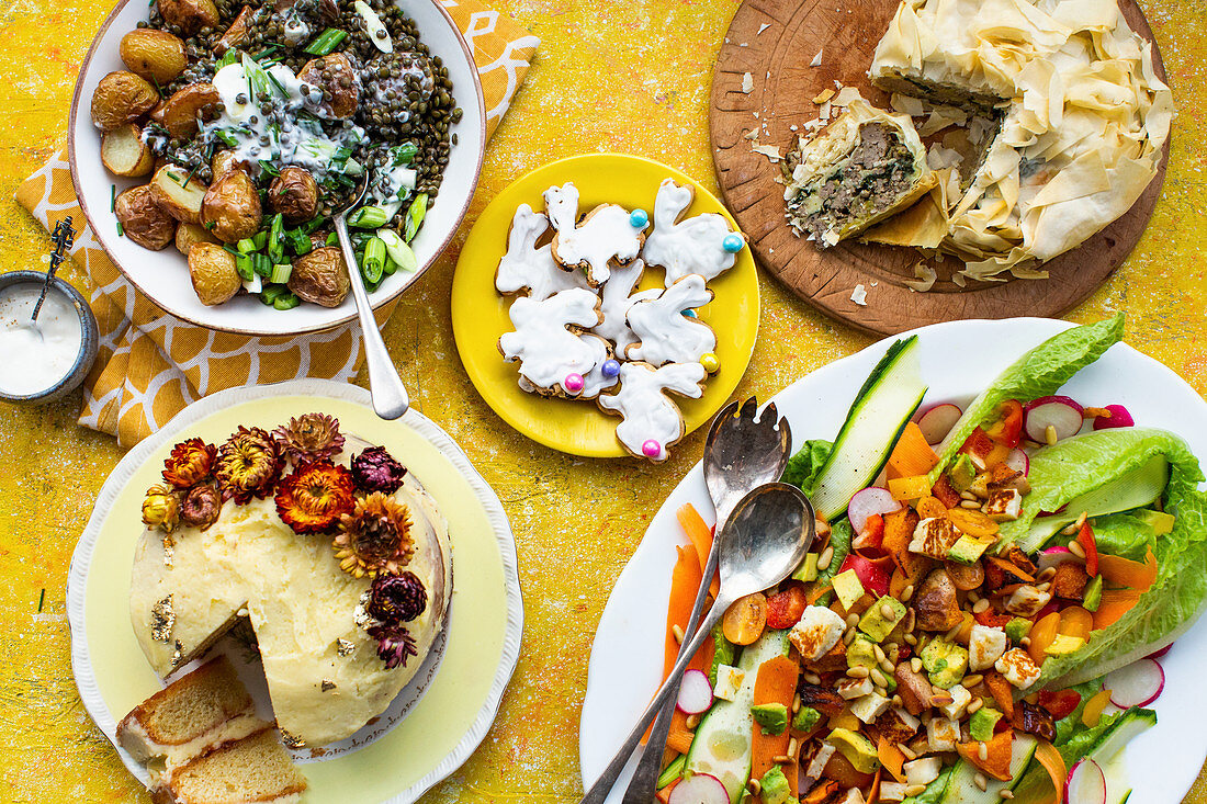 An Easter lunch with a vegetable salad, puff pastry tart, biscuits, fried potatoes and lemon cake