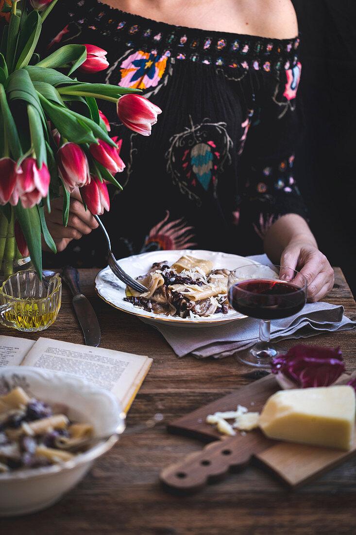 Frau isst Nudeln mit Radicchio, Pancetta und Parmesan