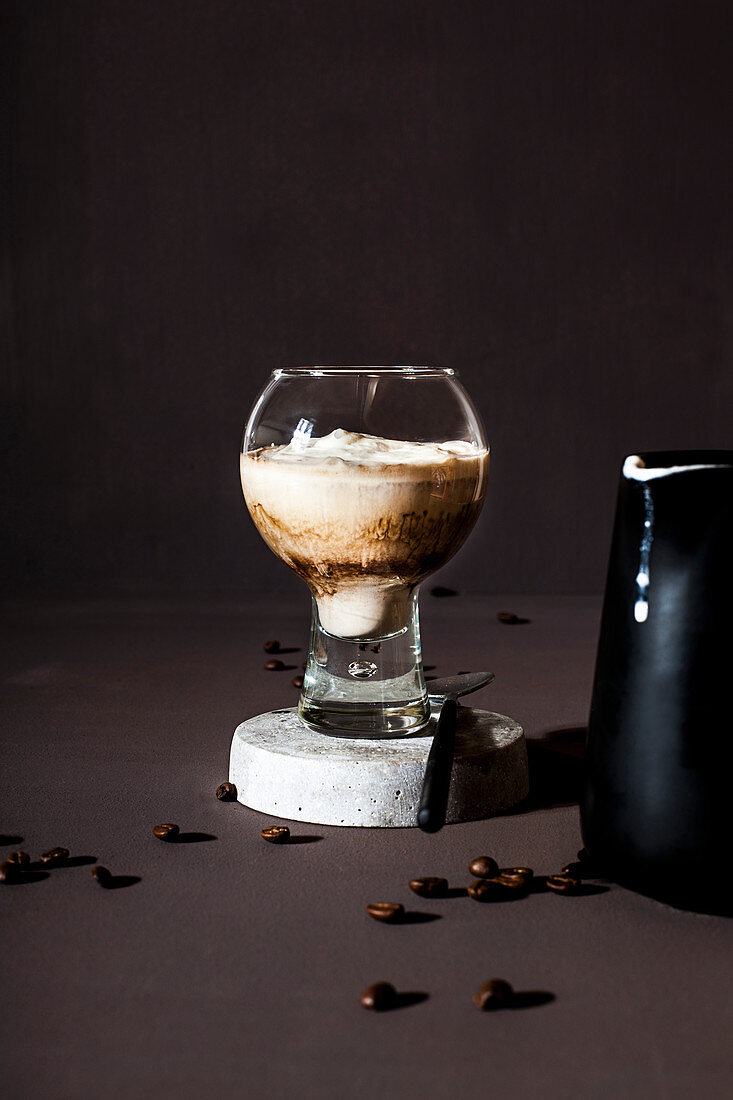 A coffee drink with cream in a glass