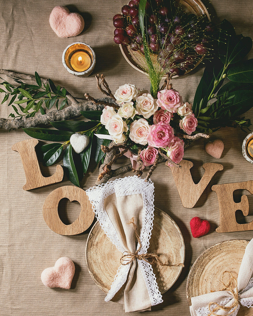 St. Valentines day or wedding romantic table setting with wooden letters love, needle felted hearts, bouquet of pink roses and red grapes on natural linen tablecloth. Flat lay