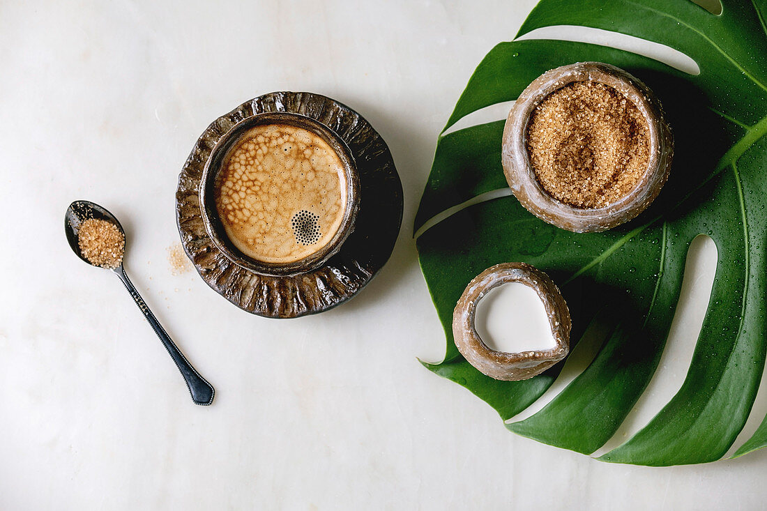 Ceramic cup of espresso coffee serving with cane sugar, jug of cream standing on monstera leaf