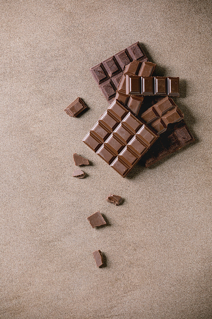 Dark and milk chocolate bar whole and chopped over brown texture background. Flat lay, space