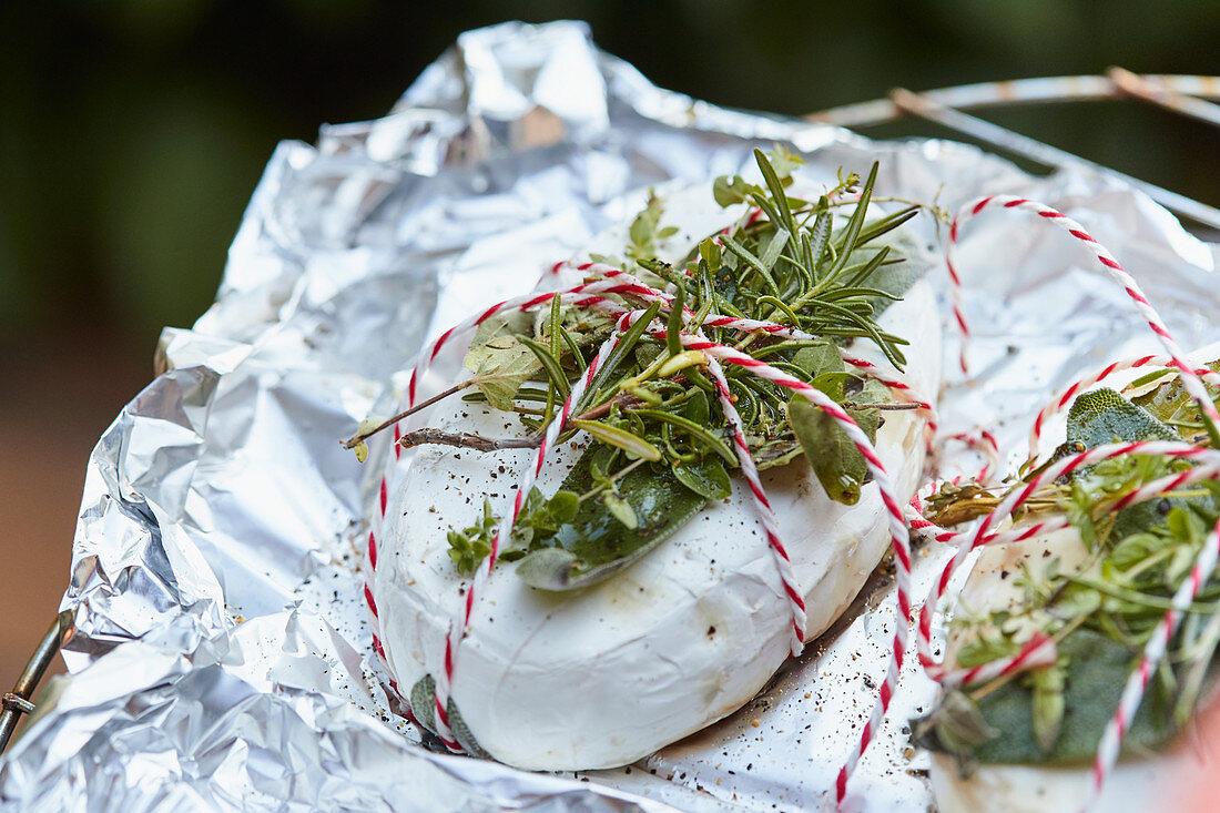 Camembert with fresh herbs in aluminium foil