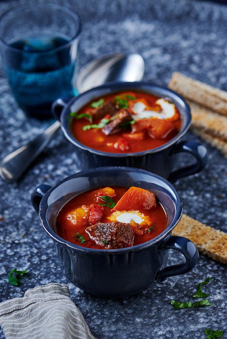 Winter goulash soup in blue soup cups