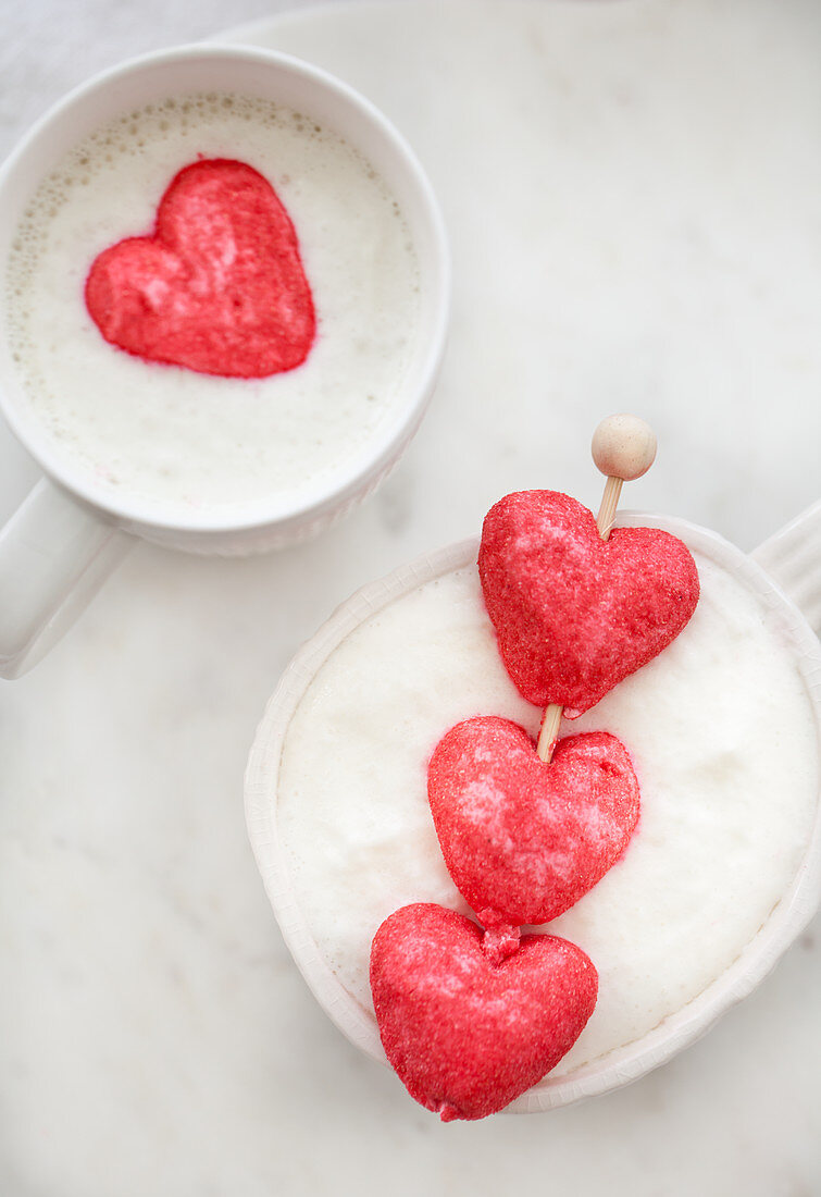 A cup of white hot chocolate with whipped cream and two pink heart marshmallows