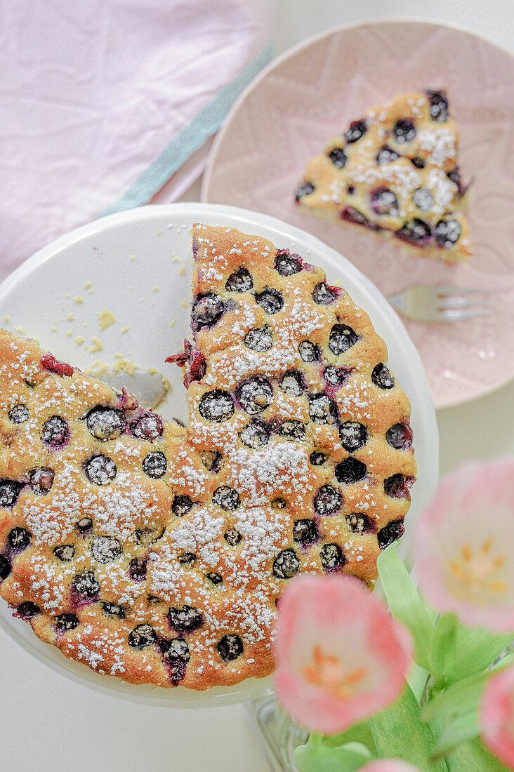Sunken blueberry cake with icing sugar, sliced