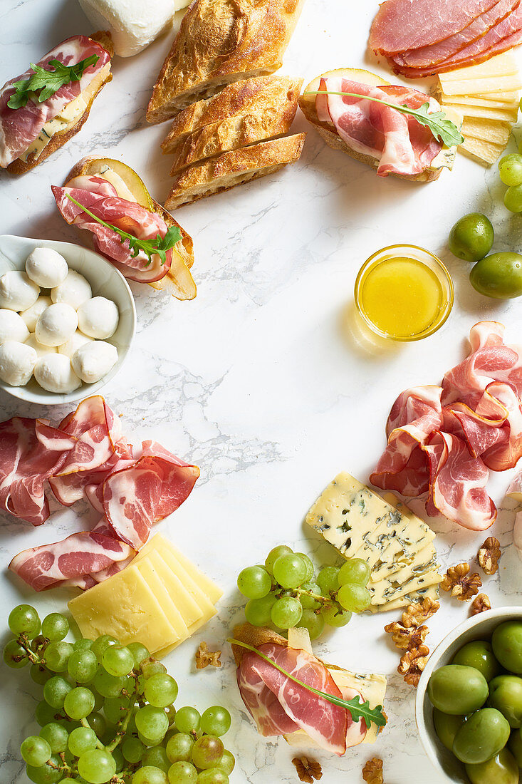 Cheese plate with brie, parmesan, cheddar and meat, fruits and baguette