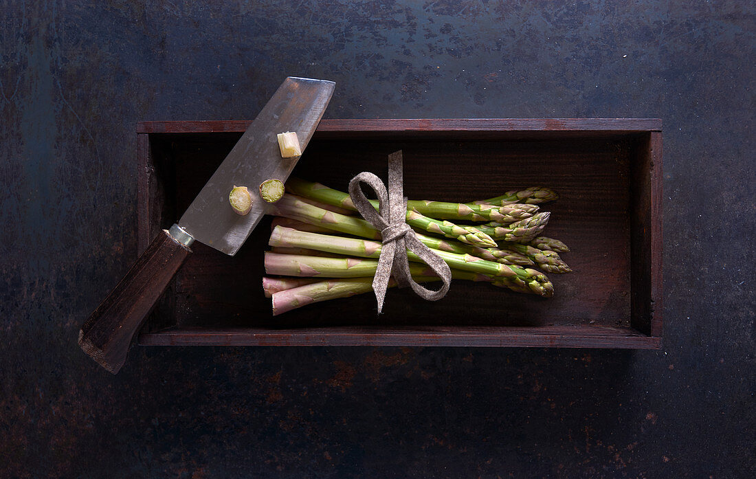 A bundle of fresh green asparagus with a knife in a wooden box on a dark surface