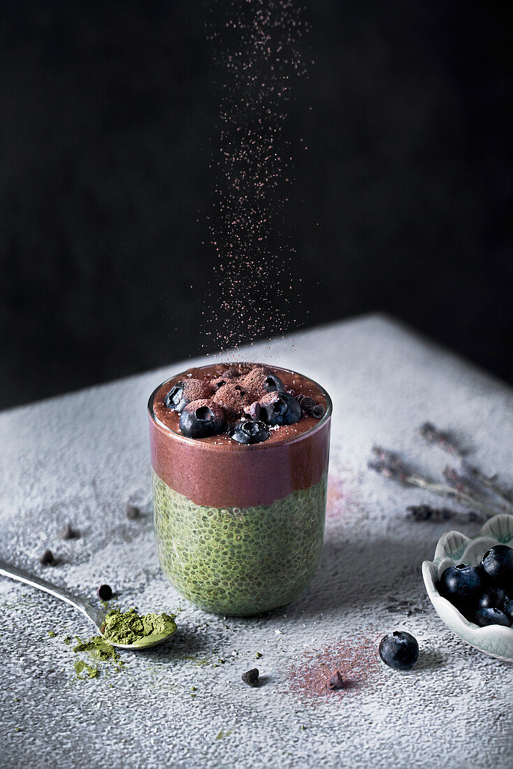 Glass of appetizing healthy matcha tea and chia seeds smoothie with chocolate and blueberries sprinkled with cocoa powder