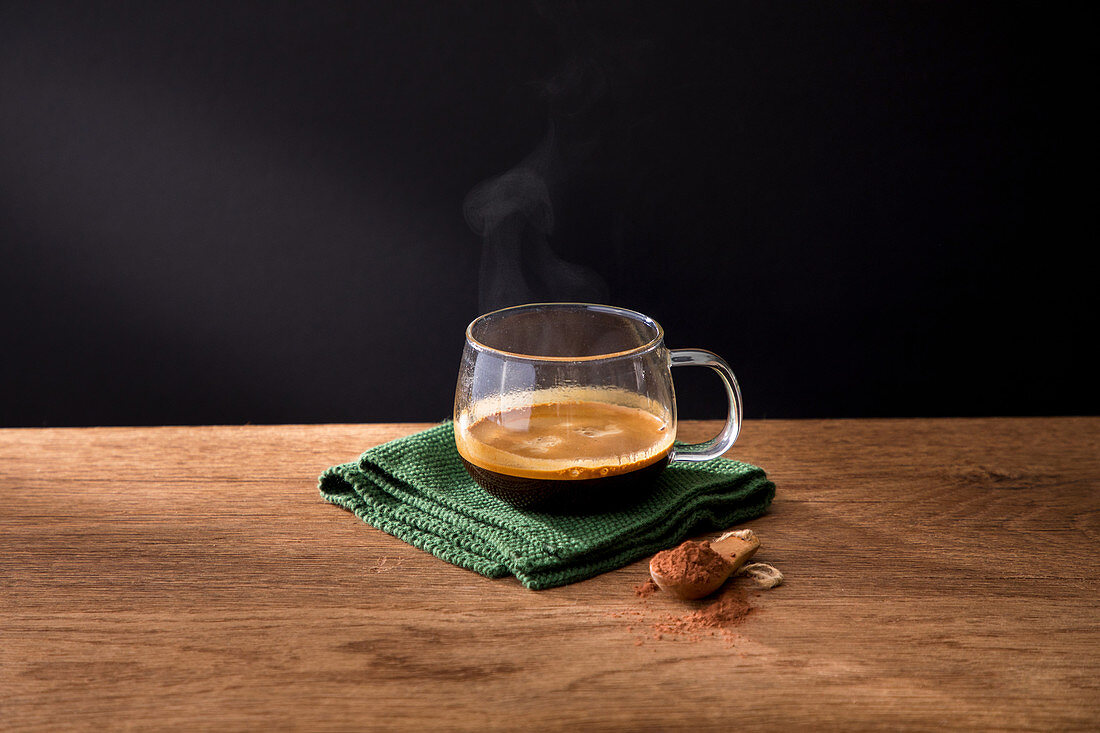 Glass cup of aromatic hot black coffee on green napkin