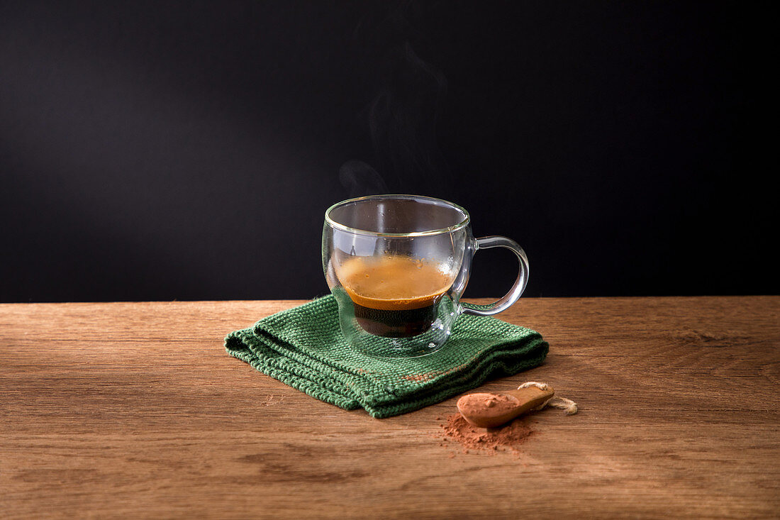 Cup of coffee and cinnamon on wooden table